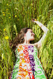 Young woman rests in a field of wildflowers. A young woman rests in a field of wildflowers Royalty Free Stock Photos