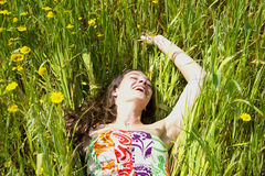 Young woman rests in a field of wildflowers. A young woman rests in a field of wildflowers Stock Image