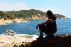 Young woman rests in front of the mediterranean sea during a spring trail Stock Image