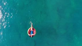 Young woman rests on a rubber ring, floating in sea. stock video