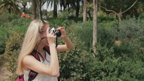 Young woman with retro camera take photos in park stock video