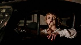 Young woman in retro car indoors. Model singing and dancing in the car looking to the camera stock video footage