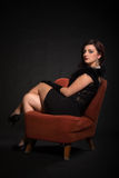 Young woman in retro clothing on old orange chair Stock Images