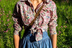 Young woman in retro clothing standing in field. Surrounded by flowers Stock Photography