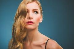 Young woman with a retro hairdo and makeup. Stock Photos
