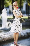 Young woman in retro style dress on a city street on a sunny day royalty free stock photo