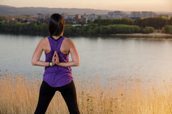 Young woman , reverse prayer yoga pose. Sunset, outdoors by the river Royalty Free Stock Photo