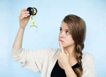 Young woman with ribbon. The girl thought about how to pack a gift Royalty Free Stock Images