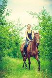 Young woman ridding on a horse Stock Photo