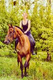 Young woman ridding on a horse. Animal, horsemanship concept. Young woman ridding on a horse through garden on sunny spring day royalty free stock images