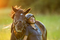 Young woman rider with her horse enjoying good mood. In evening sunset light. Outdoor lifestyle photography Stock Photography