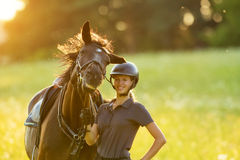 Young woman rider with her horse enjoying good mood. In evening sunset light. Outdoor lifestyle photography Royalty Free Stock Images