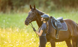 Young woman rider with her horse in evening sunset light. Outdoor photography in lifestyle mood Stock Images