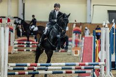 Young woman rider horse overcomes obstacles sports complex indoors. Chelyabinsk, Russia - November 22, 2015: young woman rider horse overcomes obstacles sports Stock Photos