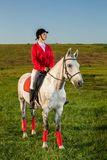 Young woman rider, wearing red redingote and white breeches, with her horse in evening sunset light. Outdoor photography in lifestyle mood royalty free stock image