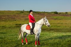 Young woman rider, wearing red redingote and white breeches, with her horse in evening sunset light. Outdoor photography in lifestyle mood stock photography