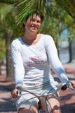A young woman rides a bicycle Stock Images