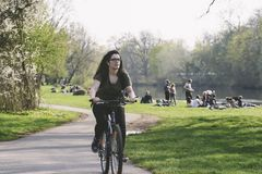 Young woman rides a bicycle along the Saale river, the city of H royalty free stock photos