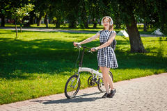 Young woman rides bicycle in the park Stock Images
