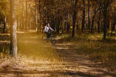 Girl rides a bike in the autumn forest stock photo