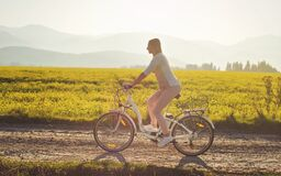Free Young Woman Rides Electric Bike Over Dusty Country Road, Strong Afternoon Sun Backlight In Background Shines On Yellow Flowers Royalty Free Stock Photo - 183559465