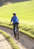 Young woman rides her bike in park Stock Photography