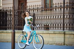 Young woman rides on retro bike holding her peonies Royalty Free Stock Photos