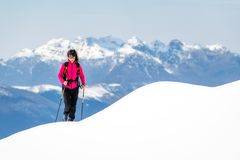 Young woman on ridge of so much snow rises towards the top in the mountains.  stock photos