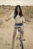 Young woman riding a beach cruiser Stock Photography