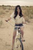 Young woman riding a beach cruiser stock photography