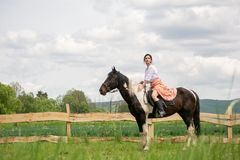 Young woman riding on beautiful horse , having fun in summer time , Romania countryside stock photography