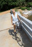 Young woman riding bicycle across river bridge next to tropical park Royalty Free Stock Photos