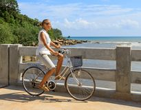Young woman riding bicycle across river bridge next to tropical park Royalty Free Stock Photography