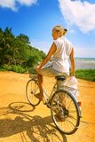 Young woman riding bicycle across river bridge next to tropical park Stock Images