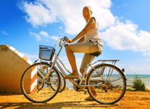 Young woman riding bicycle across river bridge next to tropical park Royalty Free Stock Images