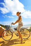 Young woman riding bicycle across river bridge next to tropical park Stock Photo