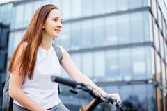 Young woman riding a bicycle in the city. The concept of an active way of life, sport and leisure.  Royalty Free Stock Photos
