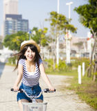 Young woman riding on bicycle in city park Royalty Free Stock Image