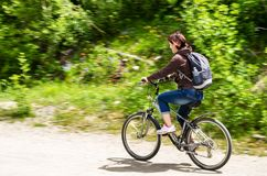 Young Woman Riding a Bicycle in the Countryside. Young Woman Riding a Bicycle on a Gravel Road through the Countryside on a Sunny Spring Day. Motion Blur Royalty Free Stock Image