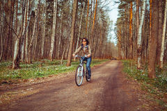 Young woman riding bicycle on a forest Royalty Free Stock Photography