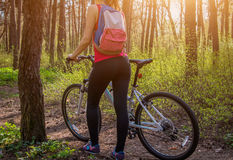 Young woman riding a bicycle in the forest Stock Images