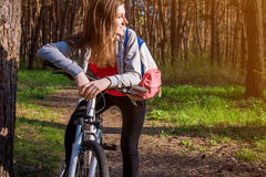 Young woman riding a bicycle in the forest Royalty Free Stock Image