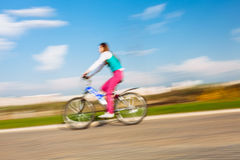 Young woman riding on bicycle in park Royalty Free Stock Photo