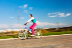 Young woman riding on bicycle in park Royalty Free Stock Photography