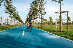 Young woman riding bicycle in the park. Royalty Free Stock Photos