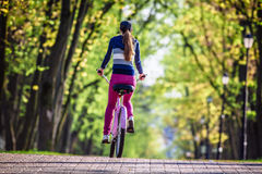 Young woman riding on bicycle in park Stock Images