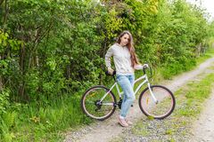 Young woman riding bicycle in summer city park outdoors. Active people. Hipster girl relax and rider bike. Cycling to work at summer day. Bicycle and ecology stock photography