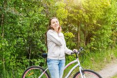 Young woman riding bicycle in summer city park outdoors. Active people. Hipster girl relax and rider bike. Cycling to work at summer day. Bicycle and ecology stock images