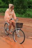 Young woman riding bicycle in tropical summer rain Stock Photography