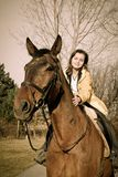 Young woman riding on big brown horse Stock Photo
